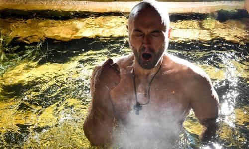 Un uomo si immerge nell'acqua gelata durante le celebrazioni dell'epifania ortodossa a Mosca, in Russia.