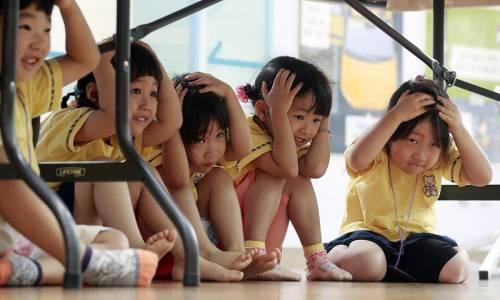 Delle bambine si riparano sotto i banchi durante un'esercitazione per apprendere come comportarsi in caso di terremoto, in una scuola materna di Seul in Corea del Sud.