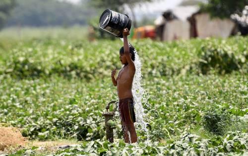 Un bambino versa l'acqua su se stesso per rinfrescarsi a New Delhi, India.